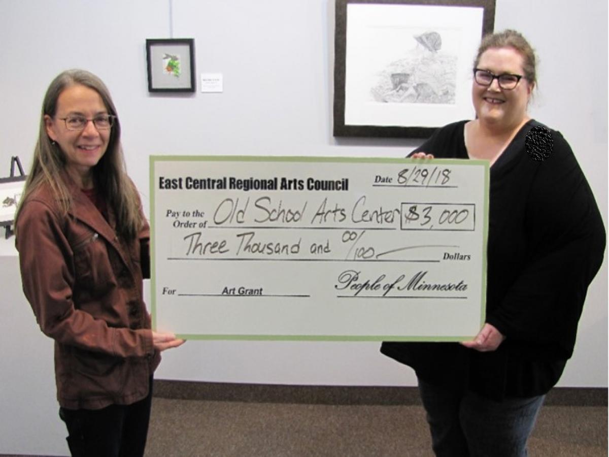 Image of ECRAC's Executive Director awarding a check for general operations