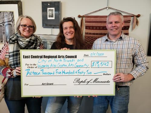 Tree Croyle and Jess Eischens of the Wyoming Area Creative Arts Community and Nate Sondrol of the City of North Branch accept funding for art projects.